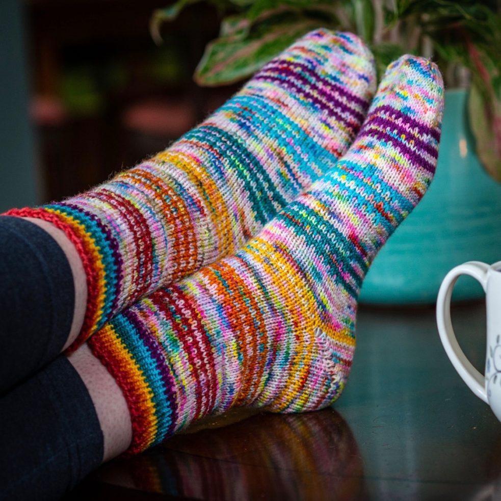 rainbow dreamboat socks feet crossed on table